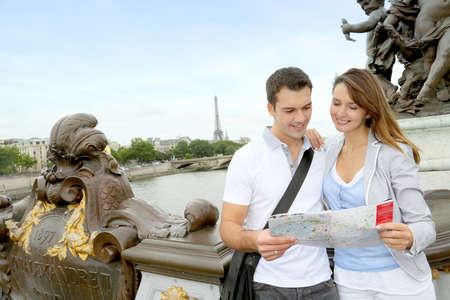 Couple reading tourist map on the Bridge Alexander the Third