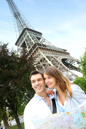 Couple reading tourist map in front of the Eiffel tower photo