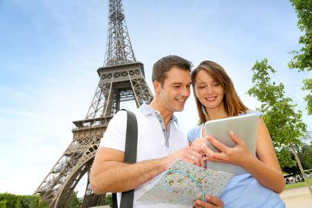 fiestas electronicas: Los turistas con tableta electr�nica en frente de la torre Eiffel