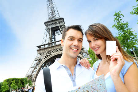 Couple in front of the Eiffel tower holding tourist pass photo