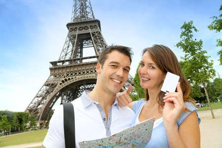 Paar vor dem Eiffelturm Holding Tourist Pass Standard-Bild - 14671111