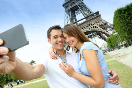 Couple in Paris taking pictures in front of Eiffel Tower photo