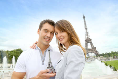 Couple standing in front of the Eiffel tower with souvenir photo