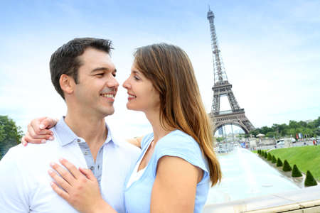 Romantic couple embracing in front of the Eiffel tower photo