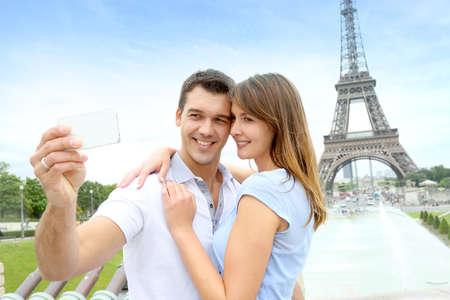 Pareja en París tomando fotos frente a la Torre Eiffel Foto de archivo