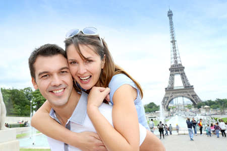 Man carrying girlfriend on his back in front of Eiffel tower photo