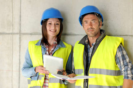 Construction team standing against building wall with blueprint Stock Photo - 15043015