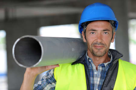Construction worker on site holding pipe Stock Photo