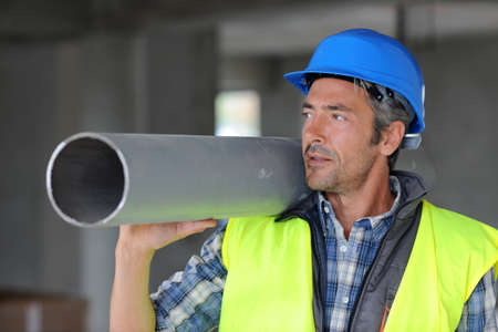 Construction worker on site holding pipe photo