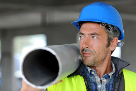 btp: Construction worker on site holding pipe Stock Photo