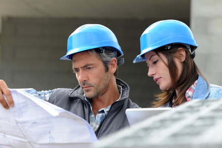Closeup of engineers reading plan on building site Stock Photo - 15043103