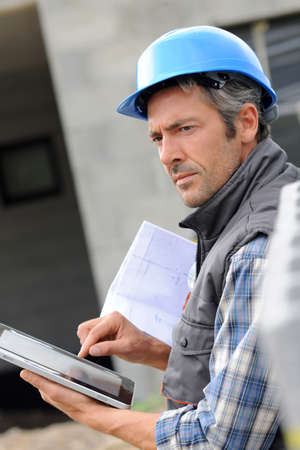 building site: Entrepreneur on construction site using electronic tablet