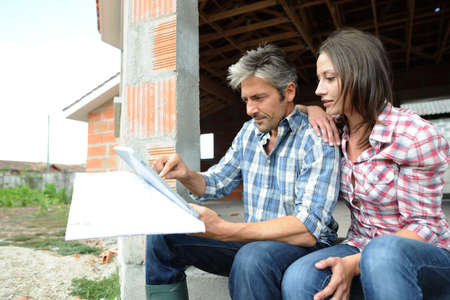 house under construction: Couple sitting in house under construction Stock Photo
