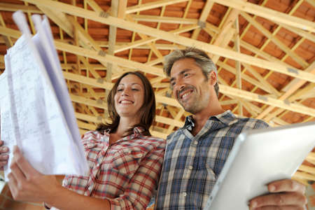 under construction: Cheerful couple standing inside house under construction Stock Photo
