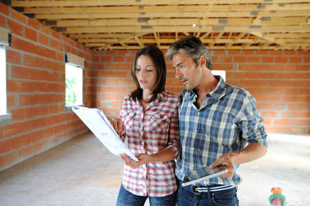 construction project: Cheerful couple standing inside house under construction Stock Photo