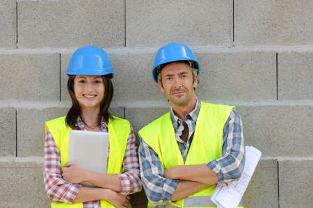 Portrait of smiling construction team standing on concrete wall photo