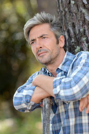 unshaved: Portrait of middle-aged man standing against tree Stock Photo