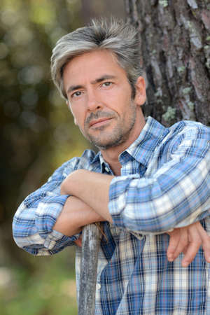 45: Portrait of middle-aged man standing against tree Stock Photo