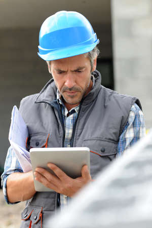 Entrepreneur on construction site using electronic tablet photo
