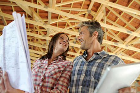 house under construction: Cheerful couple standing inside house under construction Stock Photo