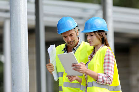 Construction people using electronic tablet on site photo