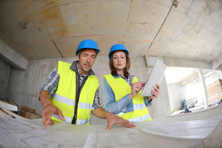 Workteam checking blueprint inside house under construction Stock Photo - 15043099
