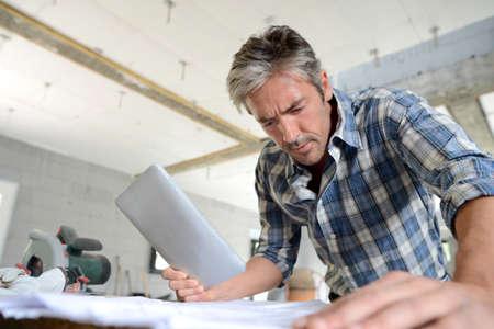 btp: Entrepreneur in house under construction checking plan