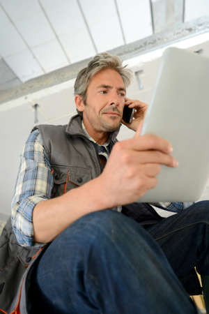 btp: Construction manager using mobile phone on building site Stock Photo