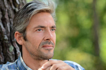 men 45 years: Portrait of middle-aged man standing against tree Stock Photo