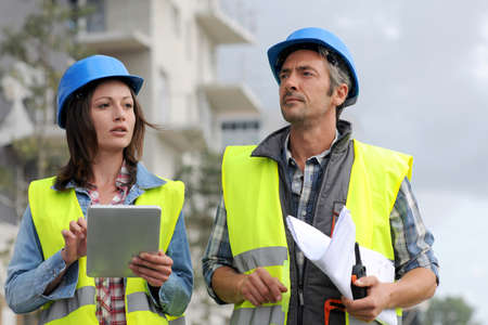 construction team: Construction people walking on building site Stock Photo