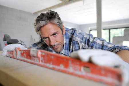 unshaved: Man using level inside house under construction