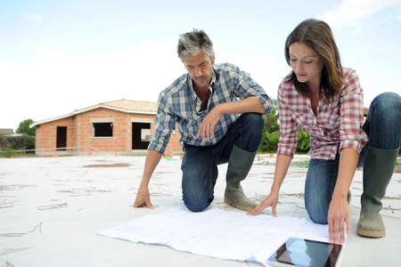mujer arrodillada: Comprobaci�n Pareja plan de construcci�n en el sitio Foto de archivo