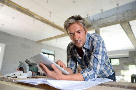 constructor: Empresario en la casa bajo el plan de construcci�n de cheques