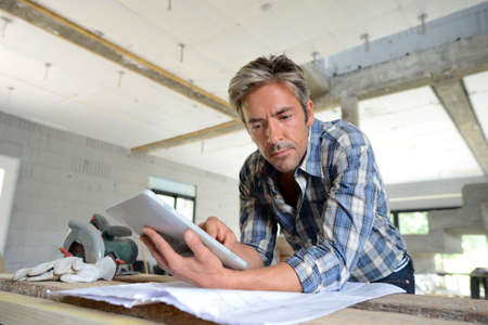 Entrepreneur in house under construction checking plan photo