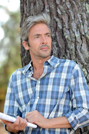 45 years old: Middle-aged man leaning against tree