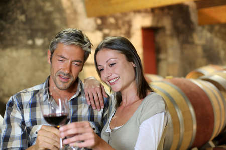 wineries: Couple of winemakers tasting red wine Stock Photo