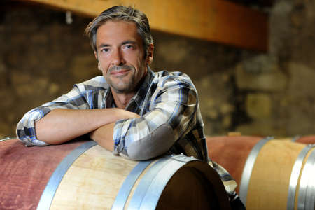 Smiling winemaker leaning on wine barrel in winery photo