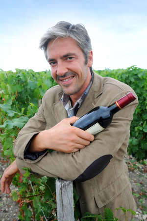 winemaker: Successful winemaker in vineyard with bottle of red wine Stock Photo