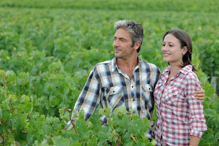 Couple of winemakers standing in vineyard photo