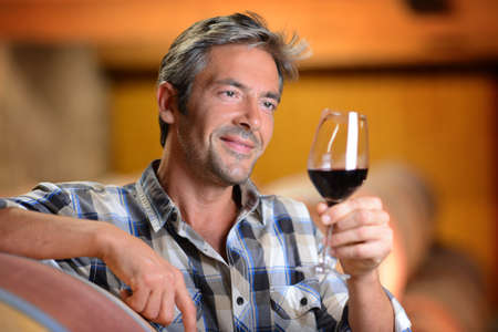 Winemaker looking at red wine in glass photo