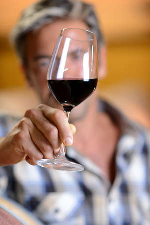 wine tasting: Focus on glass of red wine hold by winemaker