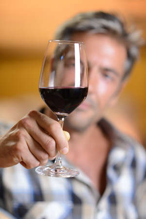 Focus on glass of red wine hold by winemaker photo