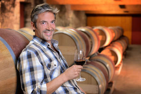 Smiling winemaker standing in wine cellar with glass photo