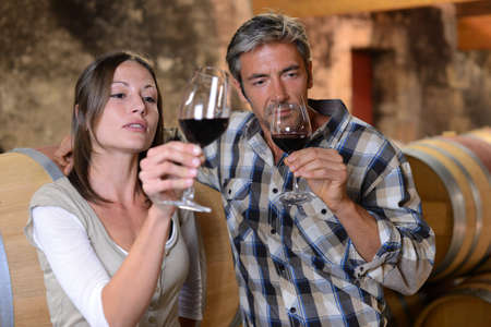 red taste: Couple of winemakers tasting red wine Stock Photo