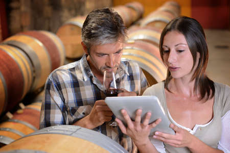 redwine: Winemakers in cellar using electronic tablet to control wine quality Stock Photo