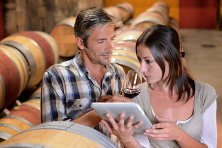 winemaker: Winemakers in cellar using electronic tablet to control wine quality Stock Photo
