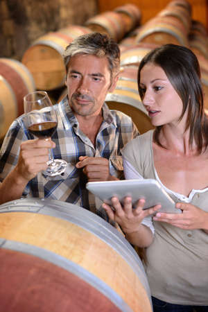 Winemakers in cellar using electronic tablet to control wine quality photo