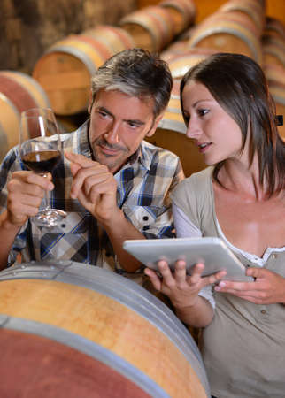 winemaker: Couple of winemaker in cellar controlling wine quality