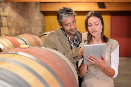 Winemakers in cellar controlling wine market prices on tablet photo