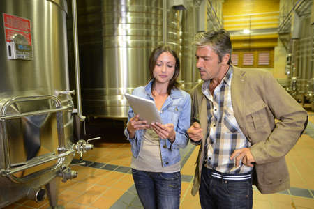 winemaking: Winemaker with client in winery looking at electronic tablet Stock Photo